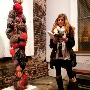 Emily Schnellbacher standing next to her piece, reading Zoe Meager's work from the chapbook